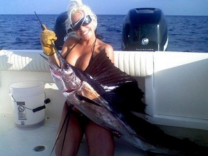 Busty blonde in a bikini fishing and holding a sailfish