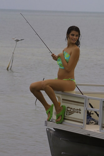 Hot girl covering up her naked breasts while fishing