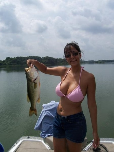 Hot woman with big tits fishing in a bikini holding up a Bass