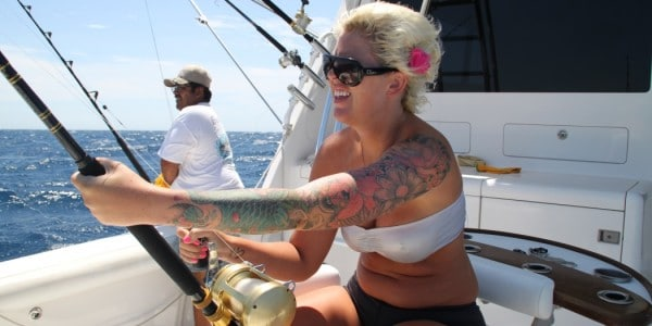 Blonde woman with tattoos fishing