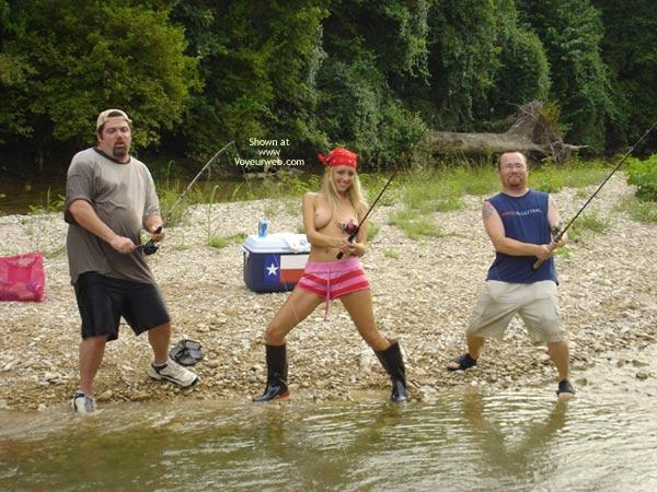 Topless girl fishing with the guys